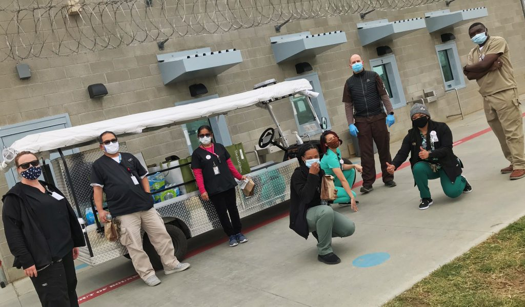 Men and women stand beside a vehicle in a prison.