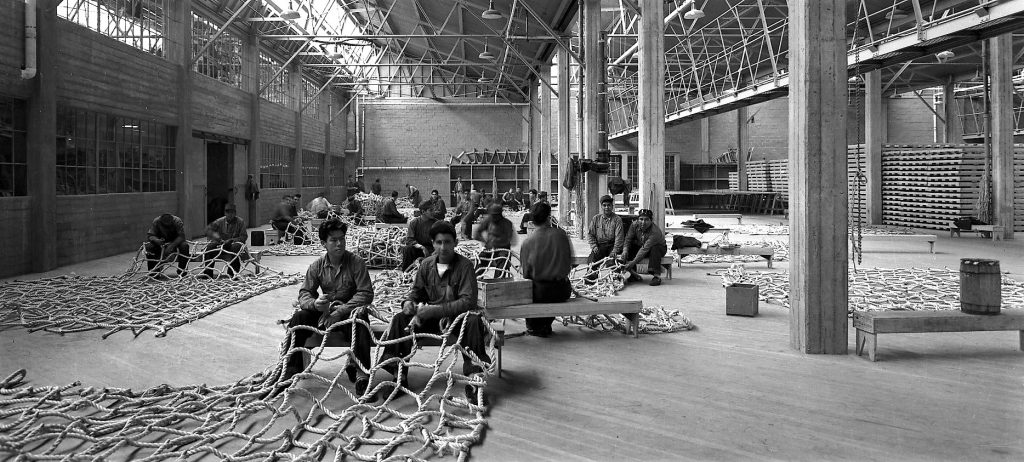 Men make rope netting in a vast warehouse style building.