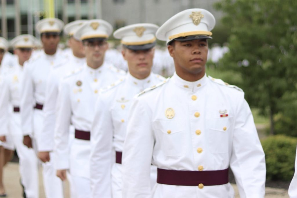 Men march while wearing formal white uniforms.