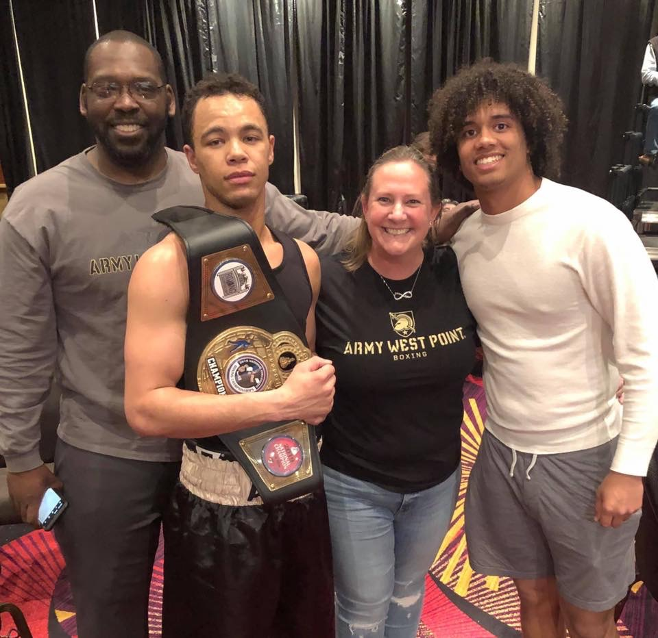 Family stands around man holding boxing belt.
