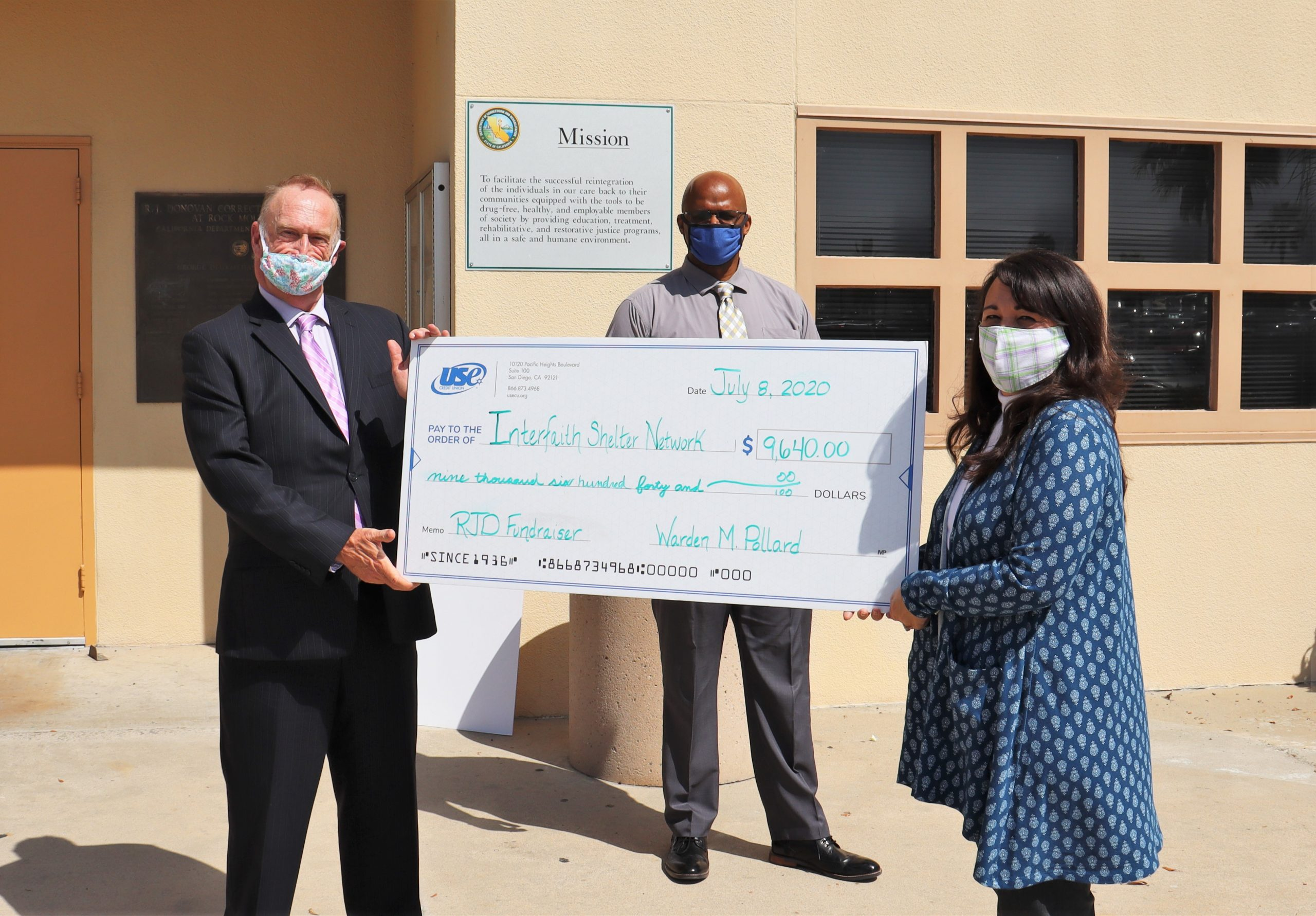 A large over-sized check is presented to a charity. Shown are two men and one woman, all wearing face coverings.