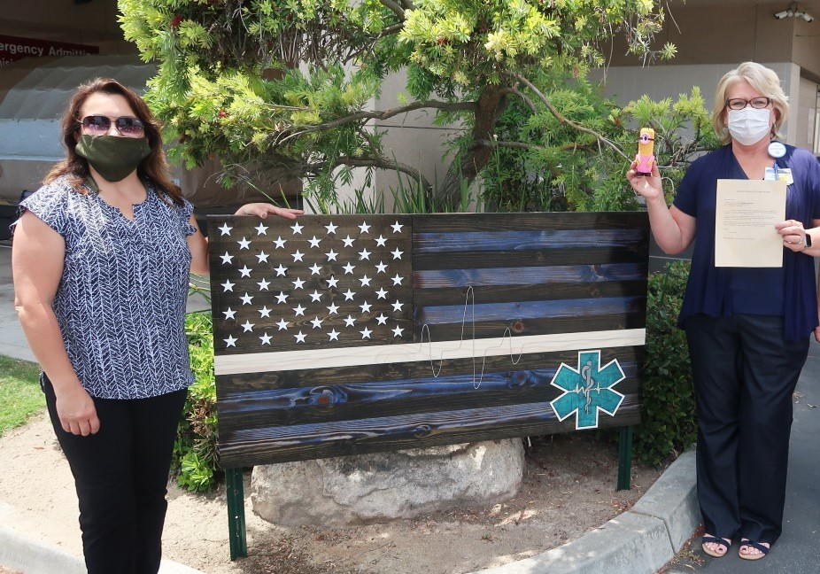 Two women stand beside a wooden flag sign. One woman holds a Minion figurine.