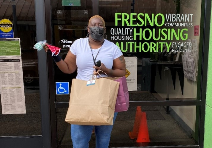 Woman stands in front of Fresno Housing Authority building while holding a bag full of face masks.