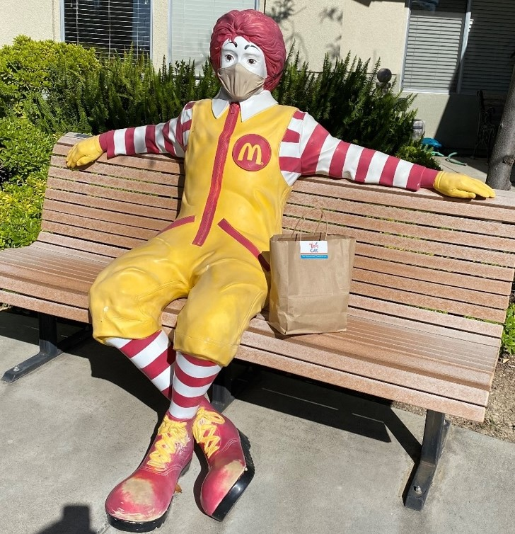 Ronald McDonald statue with bag full of masks. The statue is also wearing a mask.