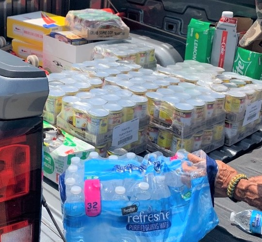 Bottled water and canned food in the back of a pickup truck.