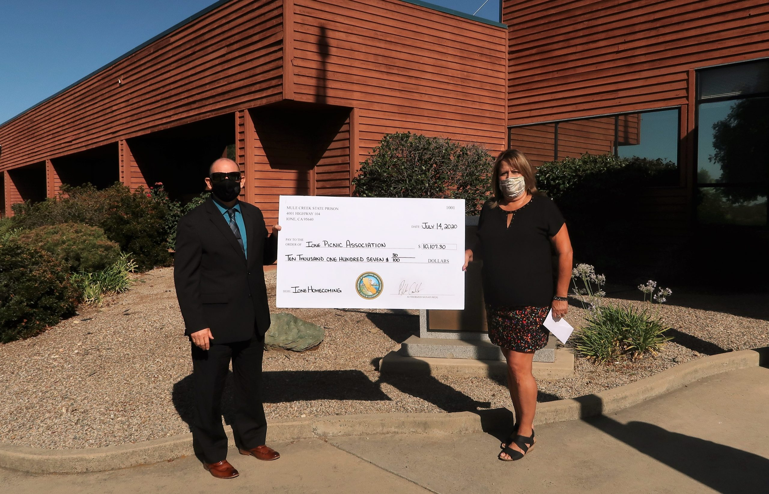 Two people hold an over-sized check while standing in front of a prison.