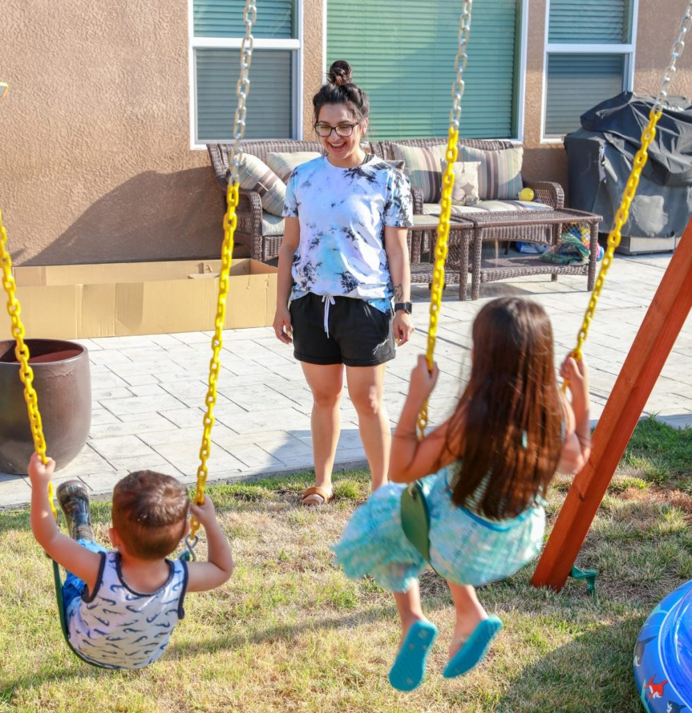 Woman watches two children play on a swing set.