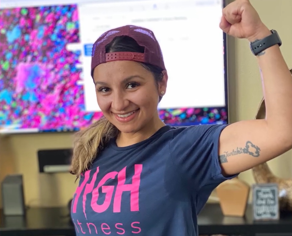 Woman flexes muscle while smiling into the camera.