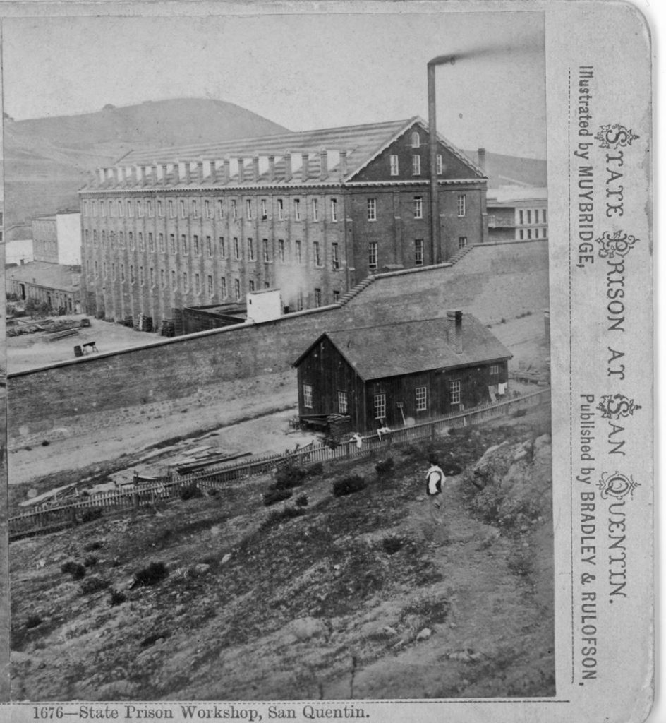 A large prison building with a smokestack.