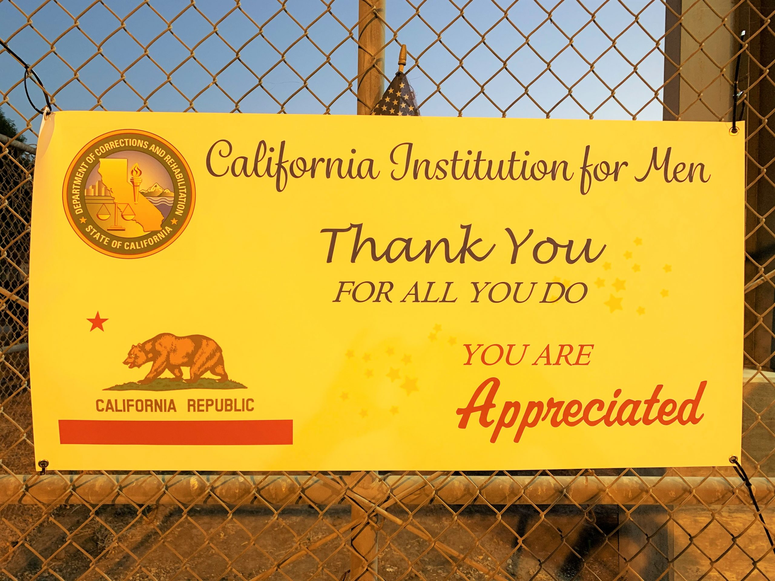 Sign hangs on a fence thanking staff at California Institution for Men.