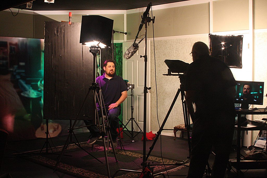 Camera man films someone seated on a chair, surrounded by theatrical lighting.