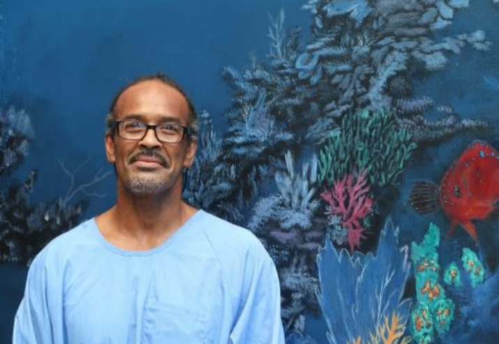 Man in blue shirt stands in front of an undersea-themed mural.