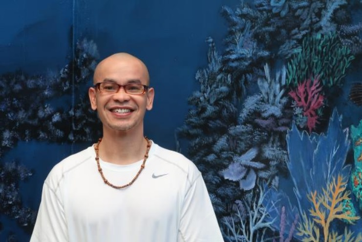 Man in white shirt stands in front of an undersea-themed mural.