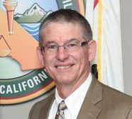 Man smiles while standing in front of a CDCR logo and California state flag.