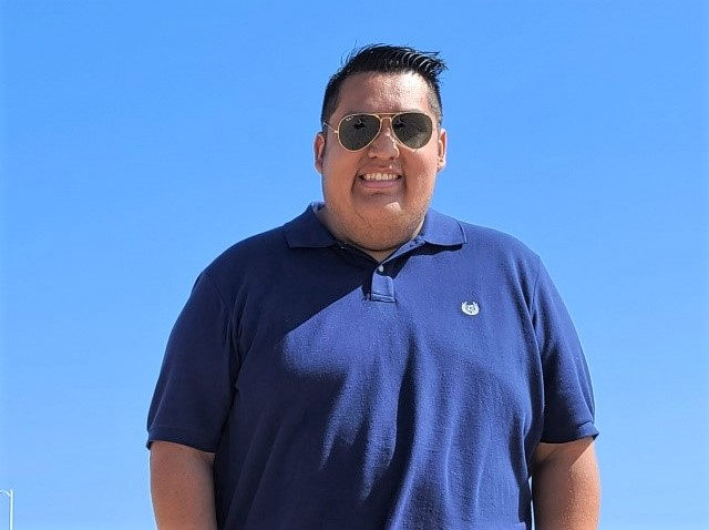 Man wearing blue shirt and sunglasses.