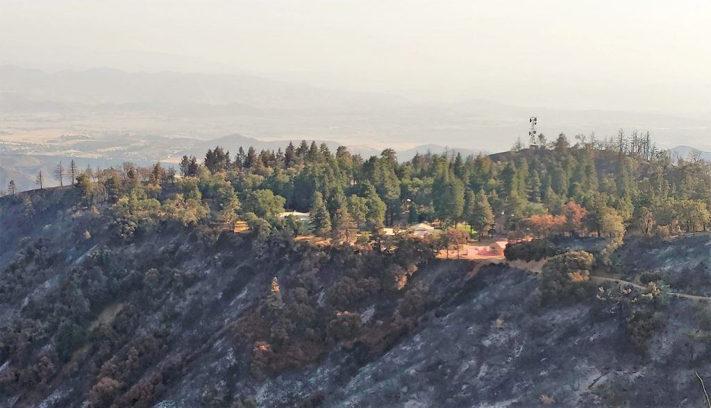 Fire camp sits atop a hill with burned out areas surrounding it.