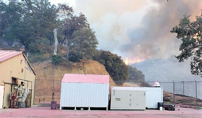 Flame can be seen on a hill behind buildings.