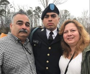 Man and woman with young man in military uniform.