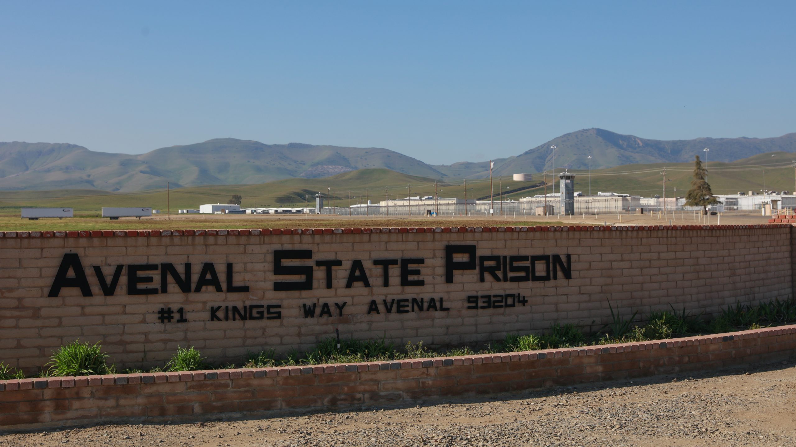 Avenal State Prison sign with prison in the background.