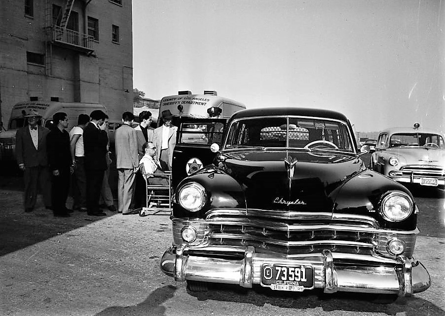 Classic vehicles and people gather outside a prison.