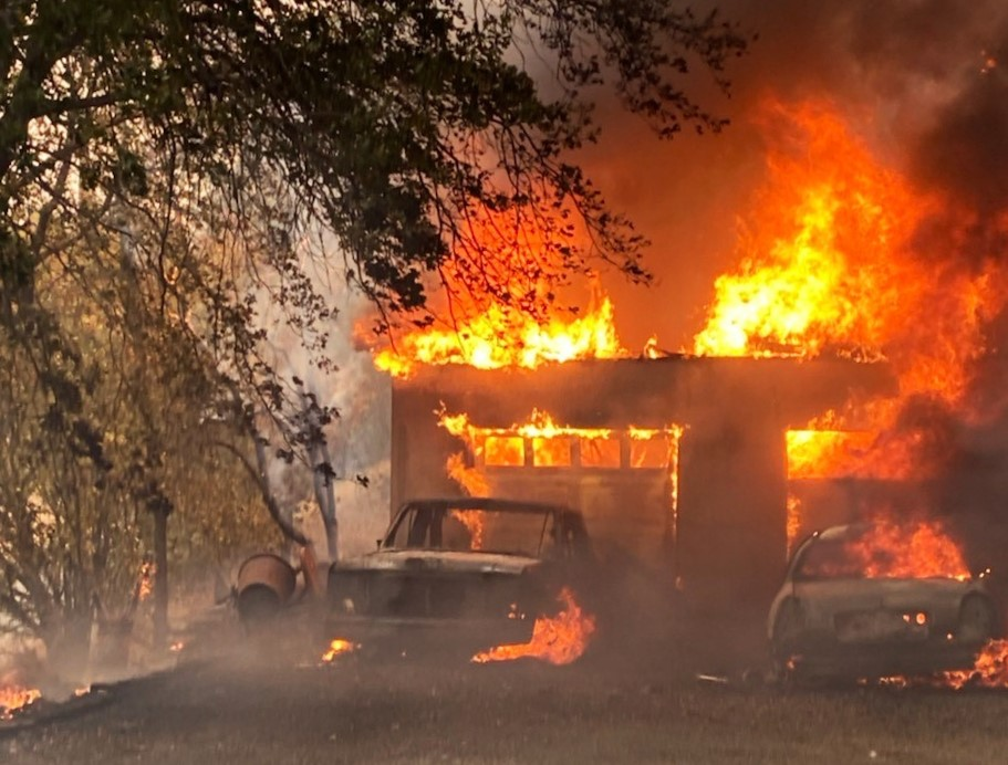 A building and two vehicles are consumed by fire.