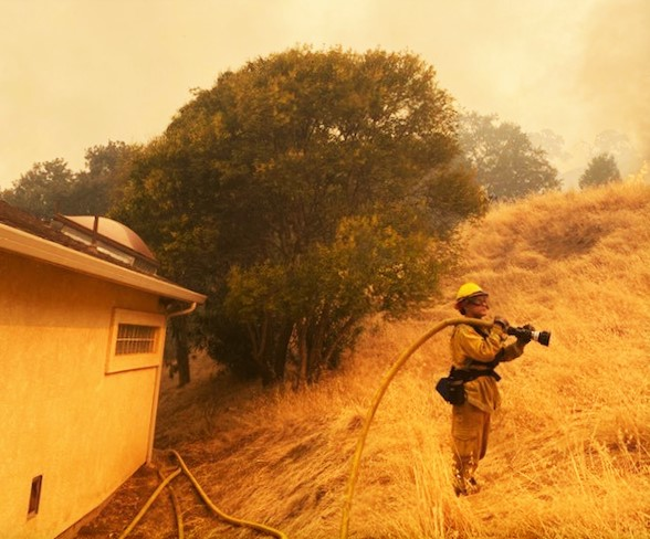 Firefighter holds fire hose as smoke clouds skies.