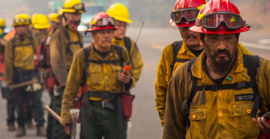 Firefighters covered in walk in a line.