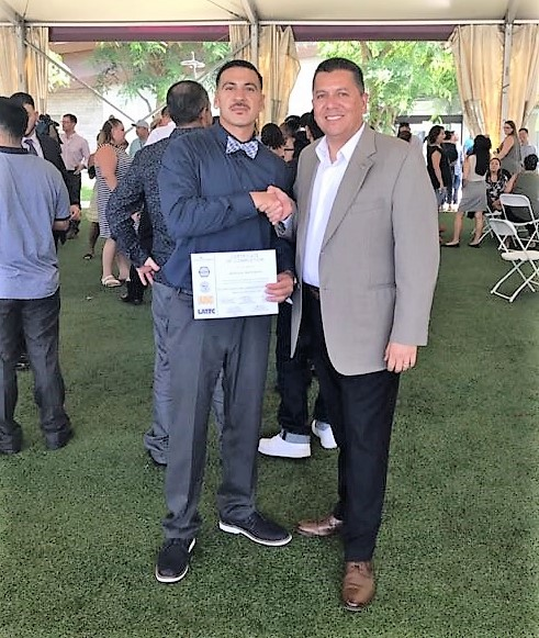 Secretary Diaz shakes hands with a formerly incarcerated man during a graduation.