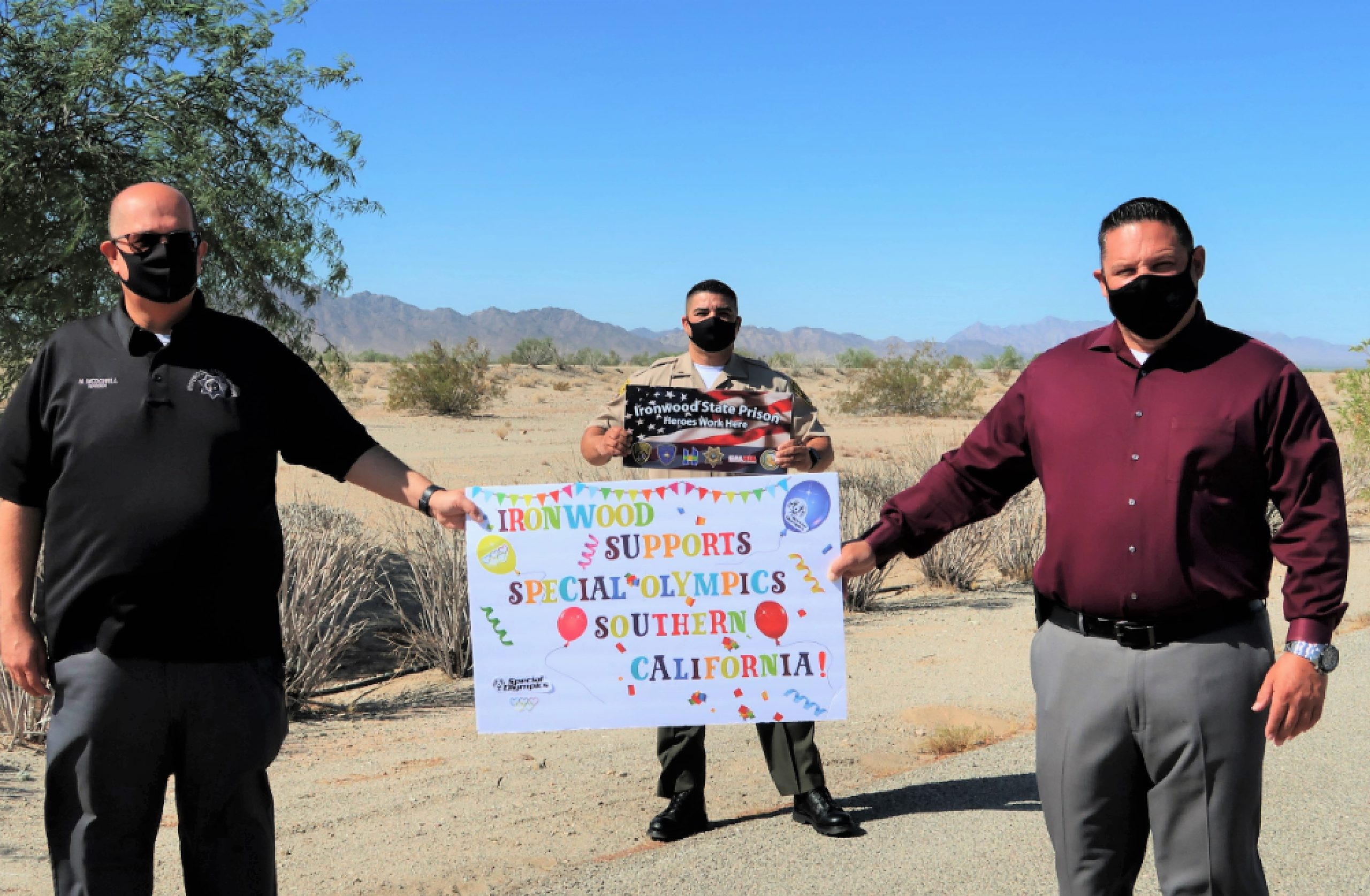 Three men hold signs saying Ironwood State Prison supports Special Olympics.