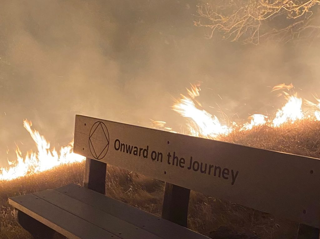 """A park bench says """"onward to the journey"""" while a fire burns in the background."""