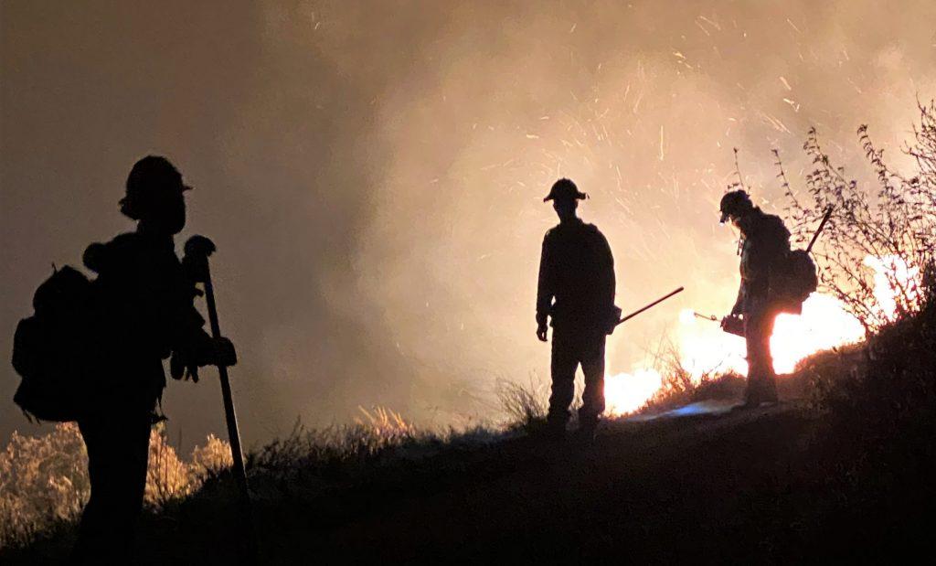 Three firefighters are silhouetted against bright flames.
