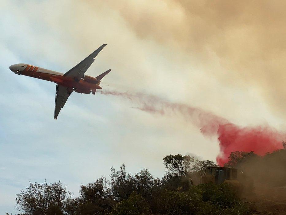 Airplane drops fire retardant on a hillside.
