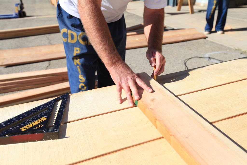 Incarcerated man marks wood for cutting at California Institution for Men.