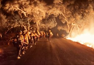 Firefighters walk along a dirt road while a fire burns on one side.