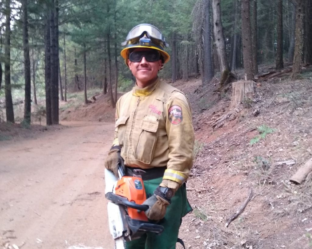 CAL FIRE firefighter Jose Morales holds a chainsaw.