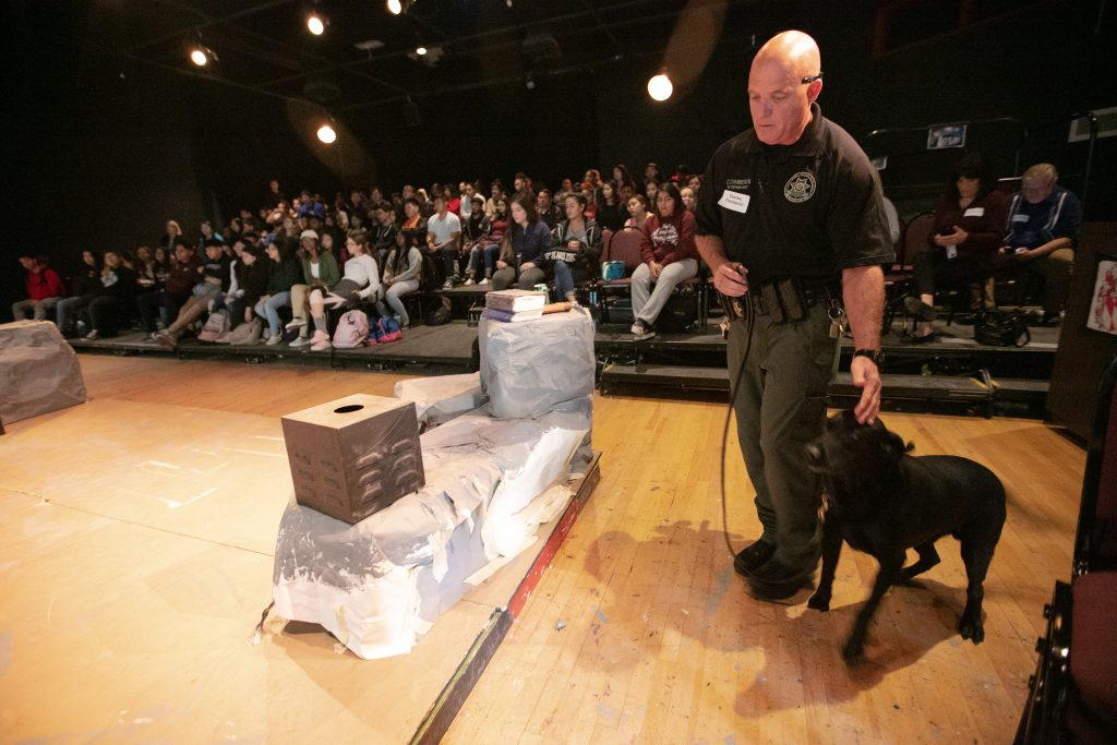 CDCR K-9 handler and dog walk on a stage while students watch.