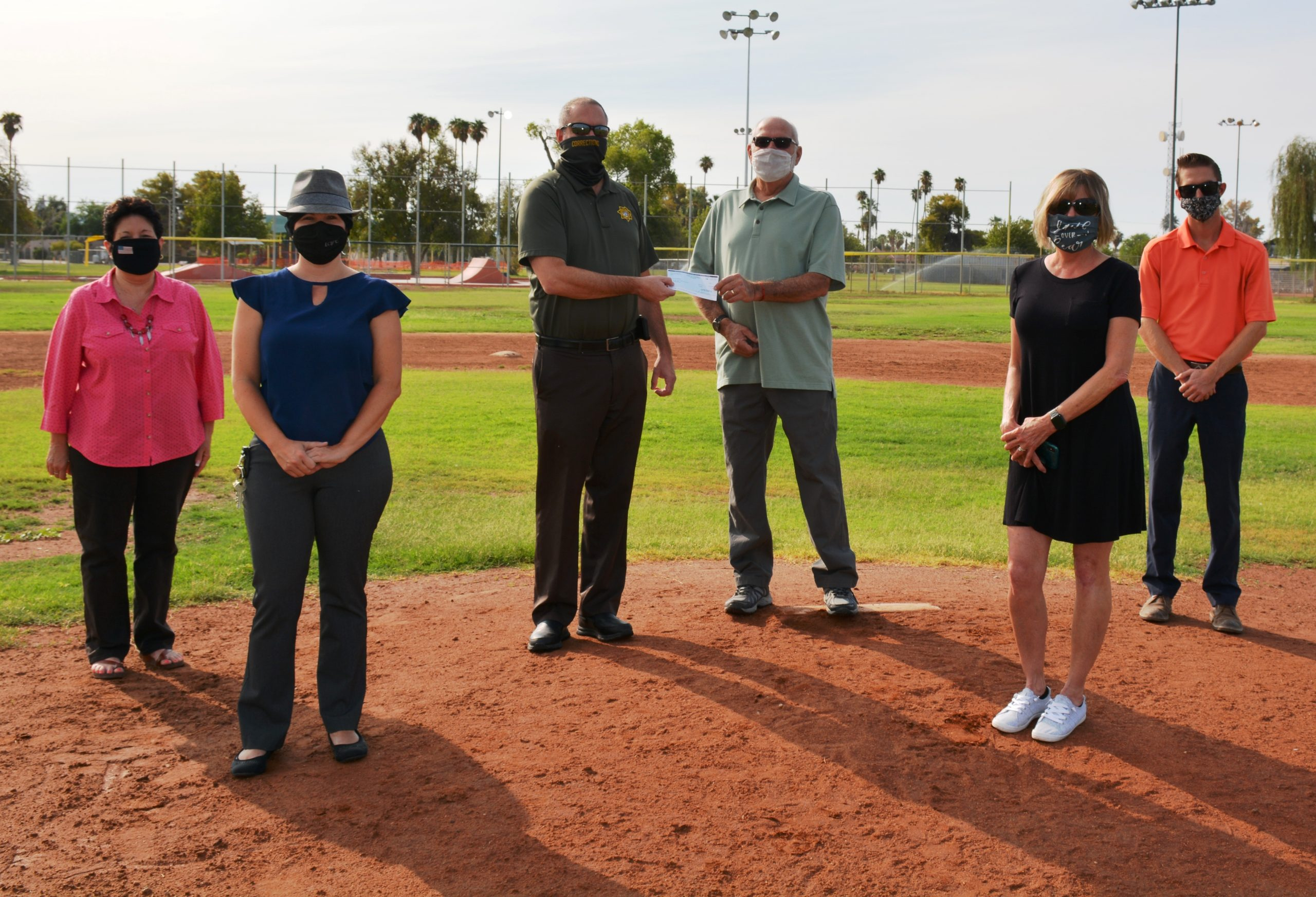 Six people wearing mask. One is handing a check to another