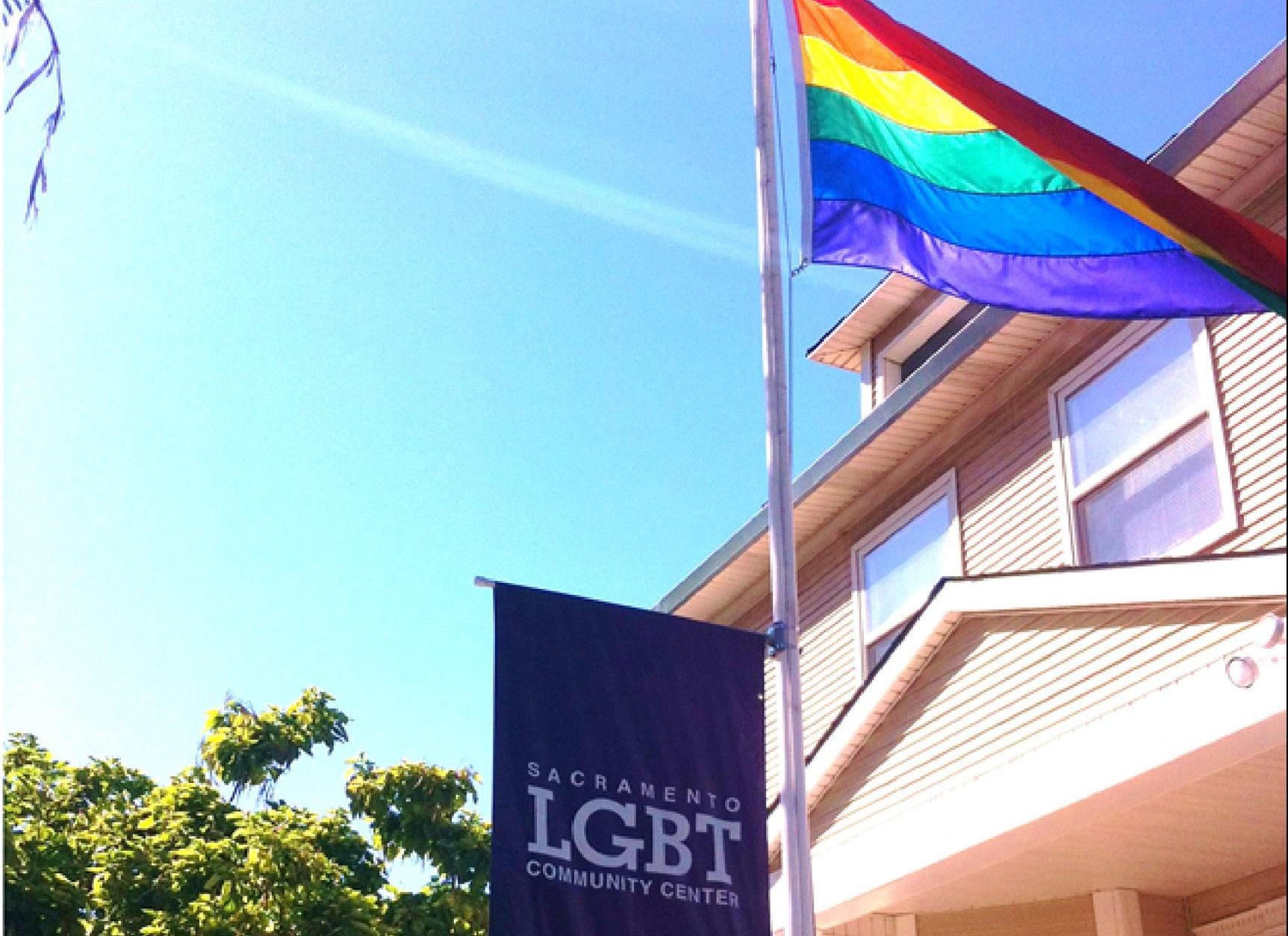 LGBT sign and rainbow flag in front of a building.