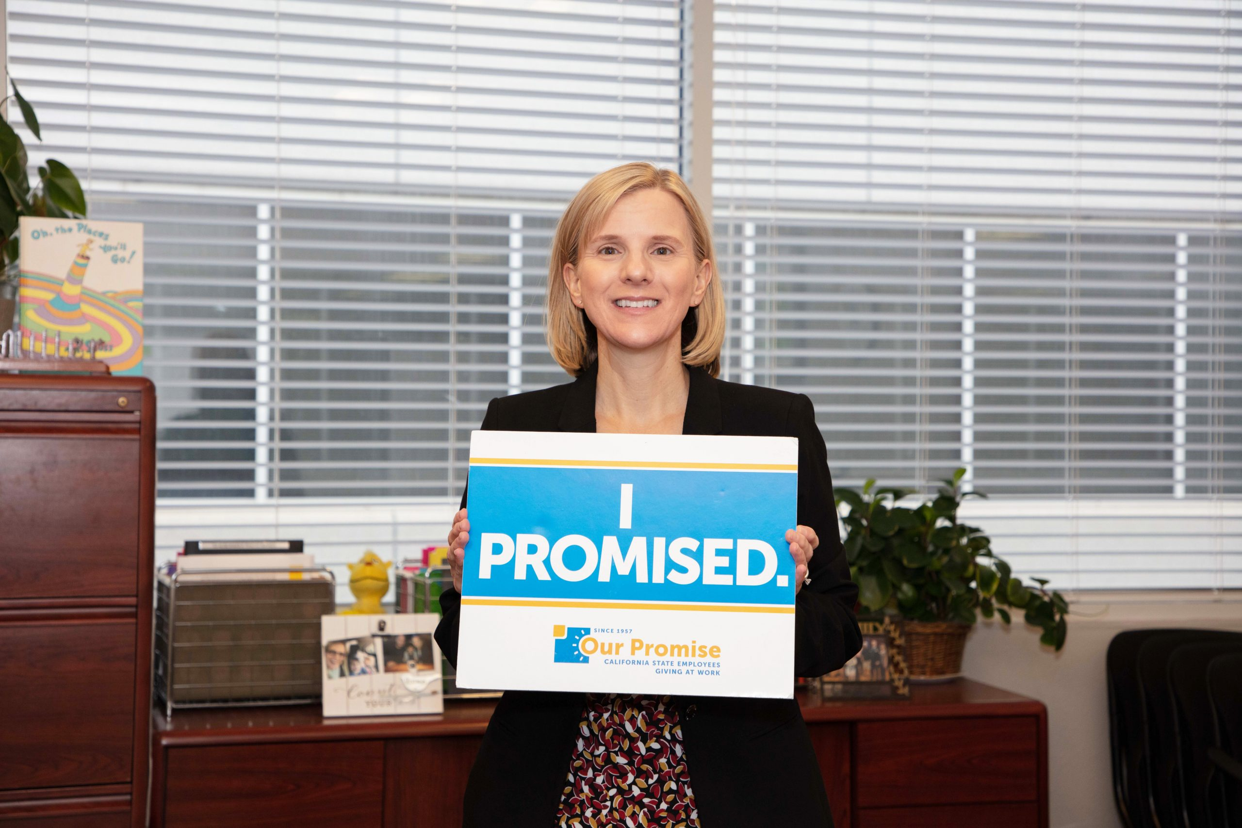 "Amy Miller holds an ""I Promised"" sign."