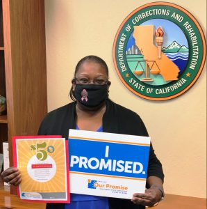 DAI Director Connie Gipson mask facing camera and holding Our Promise signs.