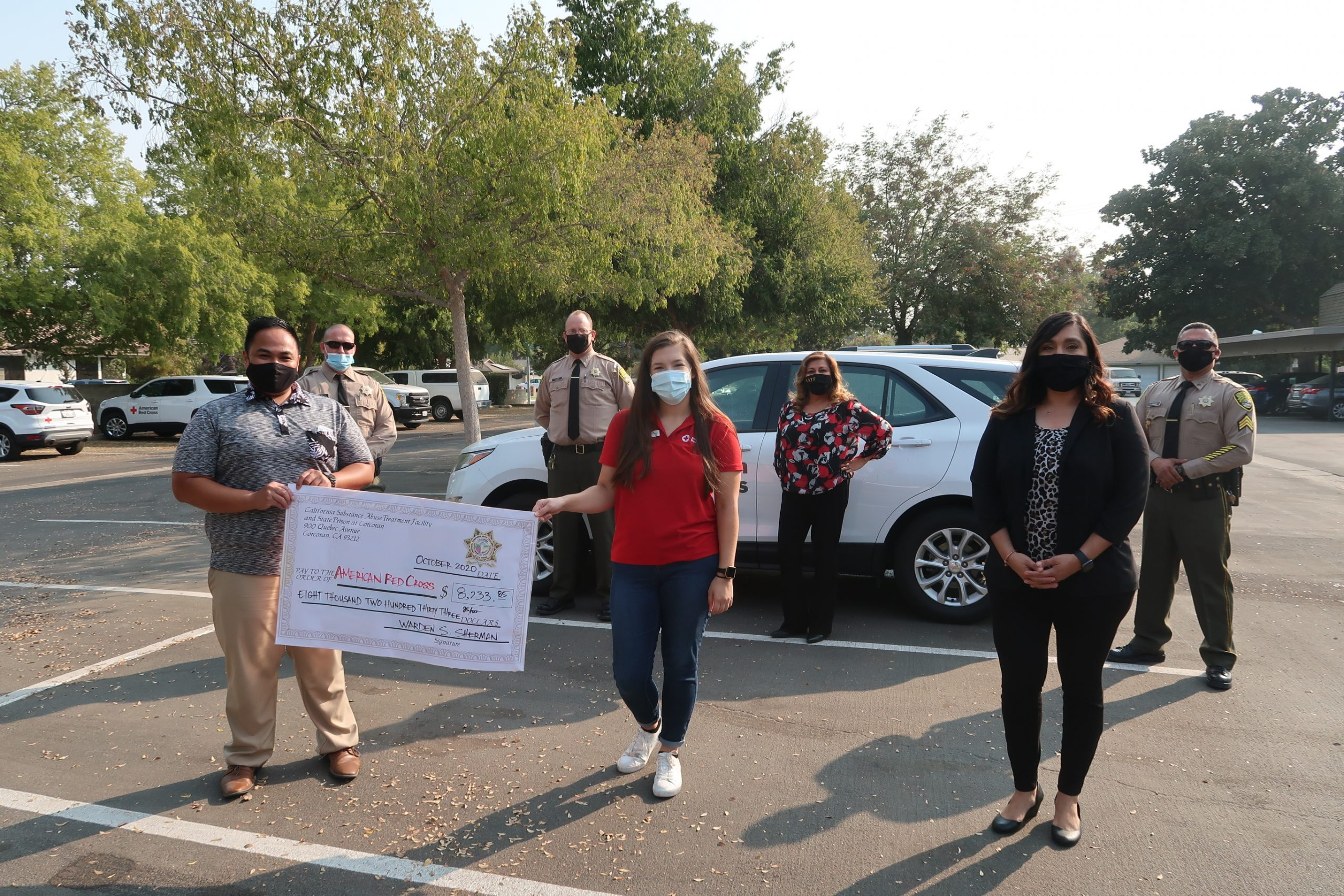 Men and women hold an oversized check.
