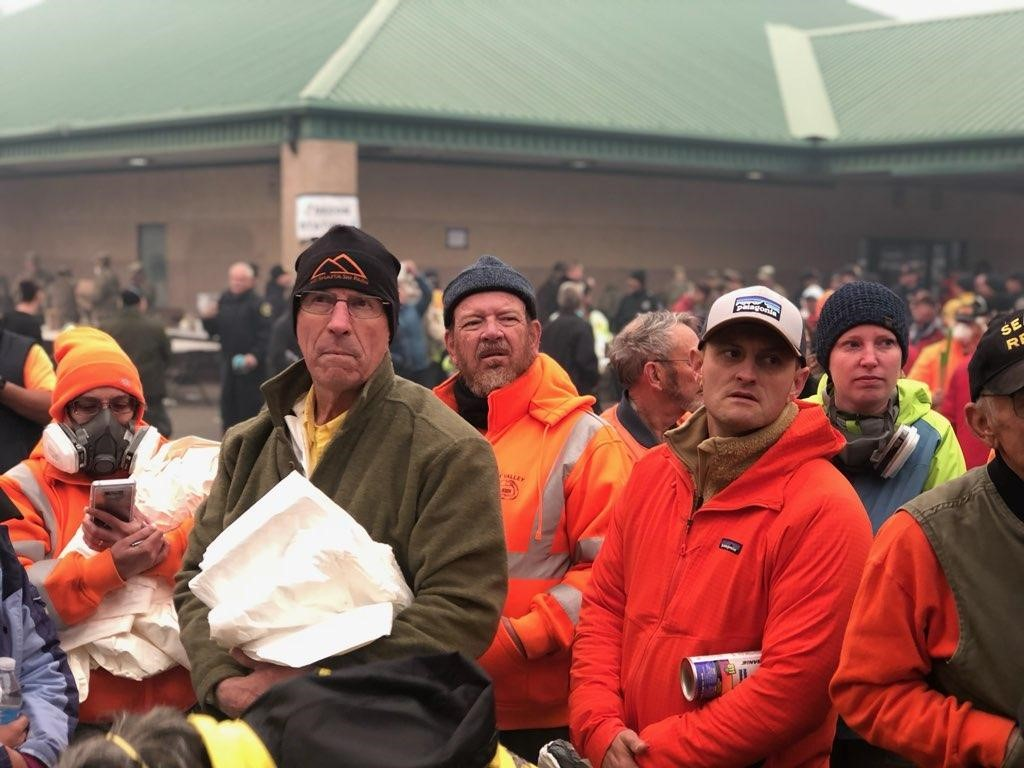 Men listen during a briefing.