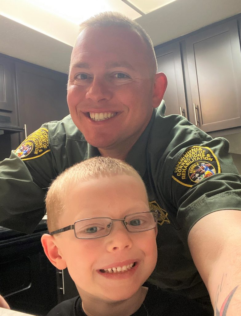 Correctional Officer Jason Williams and a little boy wearing glasses.