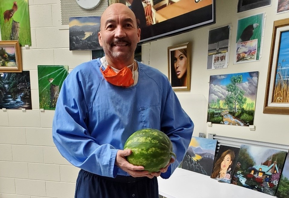 Pelican Bay State Prison inmate Jose Contreras holds a watermelon while surrounded by works of art.