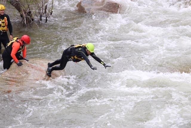 A diver jumps into river rapids.