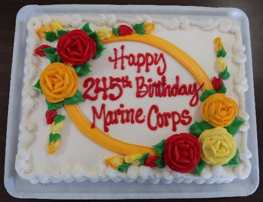 A decorated cake has the words Happy 245th Birthday Marine Corps.