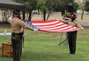 Avenal State Prison Honor Guard members begin folding a flag.