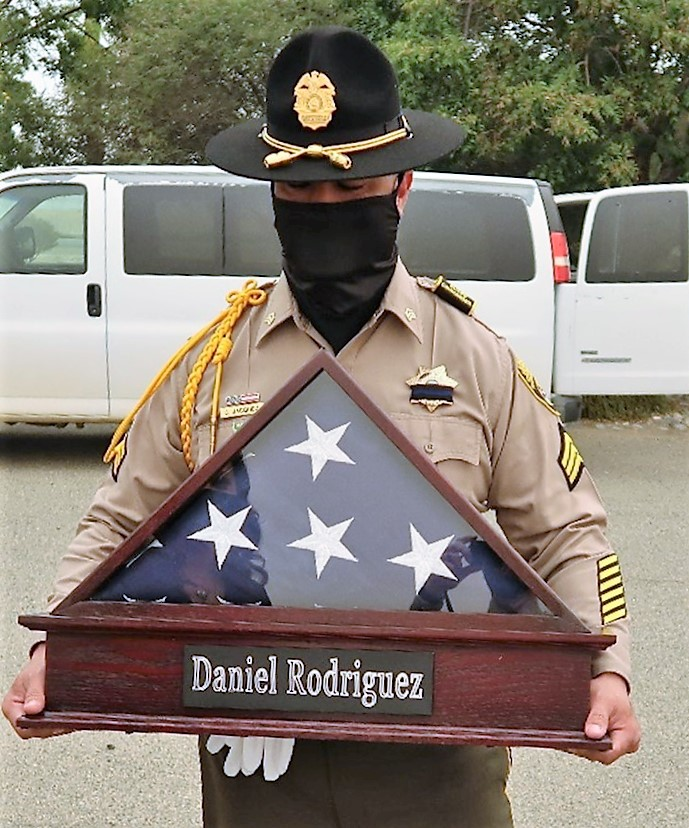 A flag honor Daniel Rodriguez is presented by the a member of the Avenal State Prison Honor Guard.