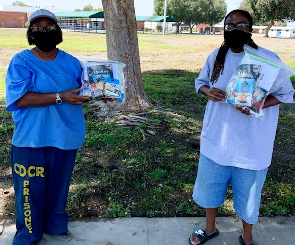 Two members of incarcerated population holding care packages