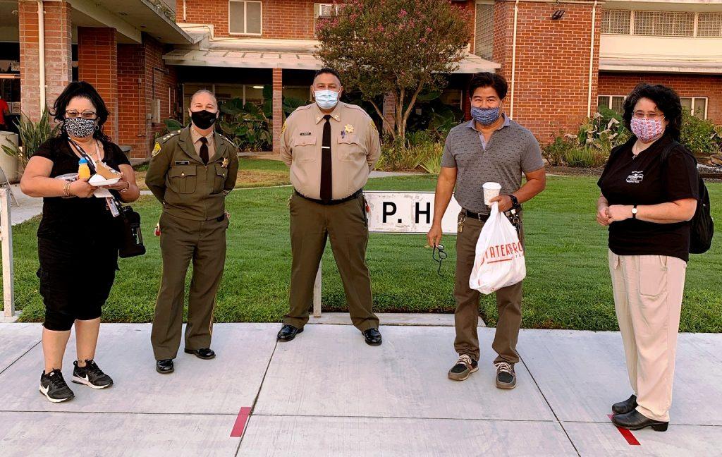 Six people wearing masks facing camera.
